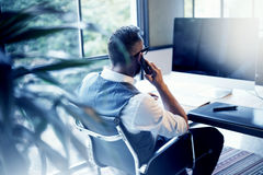 Γενειοφόρος επιχειρηματίας που φορά το άσπρο γιλέκο πουκάμισων που λειτουργεί το σύγχρονο υπολογιστή ξεκινήματος σοφιτών Δημιουργ Στοκ εικόνα με δικαίωμα ελεύθερης χρήσης