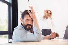 Γενειοφόρος επιχειρηματίας που χρησιμοποιεί το lap-top ενώ ξανθή επιχειρηματίας που εργάζεται με το whiteboard πίσω Στοκ Φωτογραφία