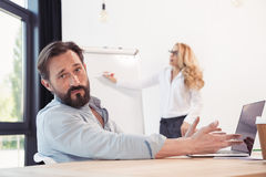 Γενειοφόρος επιχειρηματίας που χρησιμοποιεί το lap-top ενώ ξανθή επιχειρηματίας που εργάζεται με το whiteboard πίσω Στοκ Φωτογραφίες