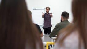Γενειοφόρος επιχειρηματίας στα γυαλιά που παρουσιάζει το νέο πρόγραμμα στους συνεργάτες με το διάγραμμα κτυπήματος, εταιρική επιχ απόθεμα βίντεο