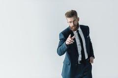 Γενειοφόρος επιχειρηματίας στο μοντέρνο κοστούμι που δείχνει στη κάμερα με το δάχτυλο Στοκ Εικόνες