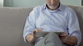 Γενειοφόρος ηλικιωμένη συνεδρίαση ατόμων στον καναπέ και χρησιμοποίηση της ταμπλέτας, που εξετάζει τις φωτογραφίες απόθεμα βίντεο