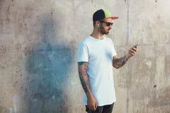 Γενειοφόρος και διαστισμένος νεαρός άνδρας που κρατά το smartphone του Στοκ Εικόνες