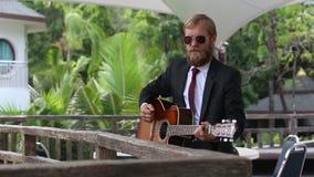 γενειοφόρος κιθάρα παιχνιδιών ατόμων από το ξύλινο εμπόδιο φιλμ μικρού μήκους