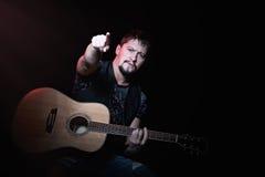Γενειοφόρος κιθαρίστας που δείχνει τα δάχτυλα στο θεατή Στοκ εικόνα με δικαίωμα ελεύθερης χρήσης