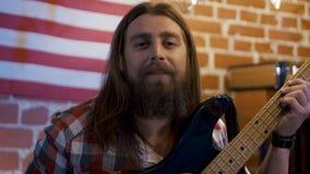 Γενειοφόρος μουσικός hipster με τη βαθιά κιθάρα απόθεμα βίντεο