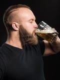 Γενειοφόρος μπύρα κατανάλωσης ατόμων από μια κούπα μπύρας πέρα από το μαύρο υπόβαθρο στοκ εικόνες
