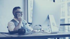 Γενειοφόρος νέος επιχειρηματίας που φορά το άσπρο πουκάμισο, το γιλέκο και την εργασία στον υπολογιστή γραφείου στη σύγχρονη σοφί στοκ εικόνες με δικαίωμα ελεύθερης χρήσης