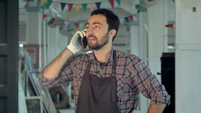 Γενειοφόρος νέος εργαζόμενος στο εργαστήριο που μιλά στο τηλέφωνο φιλμ μικρού μήκους