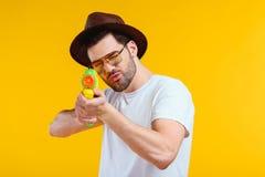 γενειοφόρος νεαρός άνδρας στο καπέλο και γυαλιά ηλίου που πυροβολούν με το πυροβόλο όπλο νερού Στοκ Φωτογραφία