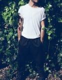 Γενειοφόρος νεαρός άνδρας με τη δερματοστιξία που φορά την κενή άσπρη μπλούζα και τα μαύρα γυαλιά ηλίου Πράσινο υπόβαθρο τοίχων κ Στοκ Εικόνες