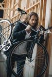Γενειοφόρος νεαρός άνδρας με το μακρυμάλλες φέρνοντας ποδήλατο στον ώμο Στοκ Εικόνες