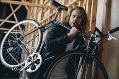 Γενειοφόρος νεαρός άνδρας με το μακρυμάλλες φέρνοντας ποδήλατο στον ώμο Στοκ φωτογραφία με δικαίωμα ελεύθερης χρήσης