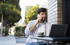 Γενειοφόρος νεαρός άνδρας με το lap-top στο τηλέφωνο έξω από έναν καφέ Στοκ εικόνες με δικαίωμα ελεύθερης χρήσης
