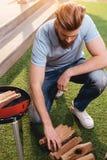 Γενειοφόρος νεαρός άνδρας που εξετάζει το καυσόξυλο για την υπαίθρια σχάρα Στοκ Εικόνες