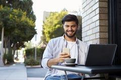 Γενειοφόρος νεαρός άνδρας που εξετάζει το smartphone του έξω από έναν καφέ Στοκ Εικόνα