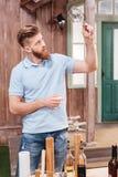 Γενειοφόρος νεαρός άνδρας που κρατά το κενό γυαλί στεμένος στον πίνακα υπαίθρια Στοκ φωτογραφία με δικαίωμα ελεύθερης χρήσης