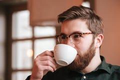Γενειοφόρος νεαρός άνδρας που φορά τα γυαλιά που πίνουν τον καφέ Στοκ Εικόνες