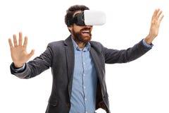 Γενειοφόρος νεαρός άνδρας που χρησιμοποιεί μια κάσκα VR Στοκ φωτογραφία με δικαίωμα ελεύθερης χρήσης