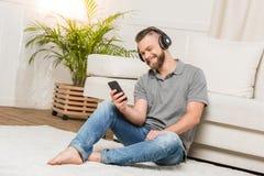 Γενειοφόρος νεαρός άνδρας στα ακουστικά που χρησιμοποιούν τη μουσική smartphone και ακούσματος στο σπίτι Στοκ Φωτογραφίες