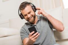 Γενειοφόρος νεαρός άνδρας στα ακουστικά που χρησιμοποιούν τη μουσική smartphone και ακούσματος στο σπίτι Στοκ εικόνα με δικαίωμα ελεύθερης χρήσης