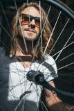 Γενειοφόρος νεαρός άνδρας στα γυαλιά ηλίου που θέτουν με τη ρόδα ποδηλάτων Στοκ Εικόνα