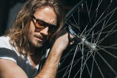 Γενειοφόρος νεαρός άνδρας στα γυαλιά ηλίου που θέτουν με τη ρόδα ποδηλάτων Στοκ εικόνα με δικαίωμα ελεύθερης χρήσης