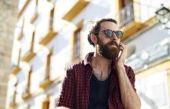 Γενειοφόρος νεαρός άνδρας στα γυαλιά ηλίου που χρησιμοποιούν το τηλέφωνο, Ibiza, Ισπανία Στοκ φωτογραφία με δικαίωμα ελεύθερης χρήσης