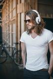 Γενειοφόρος νεαρός άνδρας στη μουσική ακούσματος γυαλιών ηλίου στα ακουστικά Στοκ Εικόνα