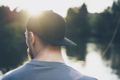 Γενειοφόρος νεαρός άνδρας φωτογραφιών που φορά τη μαύρη κενή ΚΑΠ Πράσινες υπόβαθρο λιμνών πάρκων πόλεων και επίδραση ηλιοβασιλέμα Στοκ εικόνες με δικαίωμα ελεύθερης χρήσης
