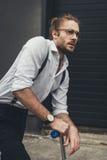 Γενειοφόρος νεαρός άνδρας eyeglasses που στέκονται στο μηχανικό δίκυκλο και που κοιτάζουν μακριά Στοκ φωτογραφία με δικαίωμα ελεύθερης χρήσης