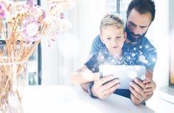 Γενειοφόρος πατέρας με το νέο γιο του που χρησιμοποιεί το PC ταμπλετών στο ηλιόλουστο δωμάτιο Παιχνίδι μπαμπάδων και μικρών παιδι Στοκ Εικόνες