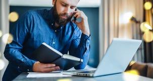 Γενειοφόρος συνεδρίαση επιχειρηματιών μπροστά από τον υπολογιστή, που μιλά στο τηλέφωνο κυττάρων κοιτάζοντας στο σημειωματάριο Σπ Στοκ φωτογραφίες με δικαίωμα ελεύθερης χρήσης