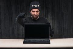 Γενειοφόρος χάκερ υπολογιστών με ένα lap-top Στοκ Εικόνα