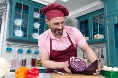 Γενειοφόρος χαμογελασμένη λαβή αρχιμαγείρων δύο μέρη του κόκκινου λάχανου στην κουζίνα Ο μάγειρας έκοψε το κόκκινο λάχανο για δύο Στοκ Εικόνες