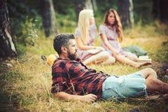 Γενειοφόρος όμορφος άνδρας και δύο αρκετά χαριτωμένες κορίτσια ή γυναίκες υπαίθριοι την ηλιόλουστη ημέρα στο δασικό υπόβαθρο στοκ εικόνες