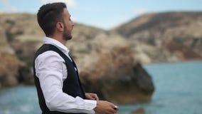 Γενειοφόρος όμορφος νεαρός άνδρας κοντά στη θάλασσα και τα βουνά που ρίχνουν τις πέτρες στο νερό o E r φιλμ μικρού μήκους