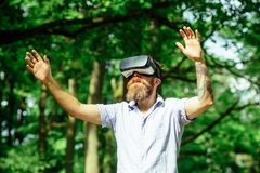 Γενειοφόρο άτομο με το ταξίδι συσκευών στο θερινό δασικό άτομο με τα γυαλιά ένδυσης VR γενειάδων ηλιόλουστο σε υπαίθριο Hipster μ Στοκ φωτογραφία με δικαίωμα ελεύθερης χρήσης