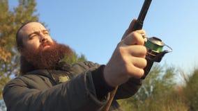 Γενειοφόρο άτομο που αλιεύει με μια ράβδο αλιείας Ο ψαράς γυρίζει τη σπείρα σε ένα ψάρι εξαγωγής περιστροφής απόθεμα βίντεο