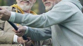 Γενειοφόρο άτομο που βοηθά το συνταξιούχο φίλο του που τραβά τα ψάρια από το νερό, αρσενικό χόμπι απόθεμα βίντεο