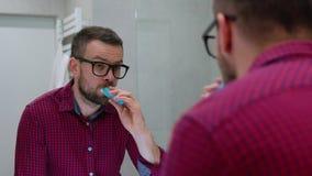 Γενειοφόρο άτομο που βουρτσίζει τα δόντια του σε ένα λουτρό το πρωί Υγιεινή πρωινού φιλμ μικρού μήκους
