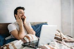 Γενειοφόρο άτομο που βρίσκεται στο κρεβάτι πρωινού με το lap-top στοκ φωτογραφίες