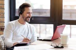 Γενειοφόρο άτομο που εξετάζει το lap-top και τις ομιλούσες σημειώσεις Στοκ φωτογραφία με δικαίωμα ελεύθερης χρήσης