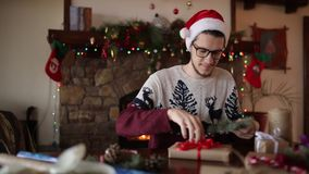 Γενειοφόρο άτομο που κάθεται και που δένει ένα τόξο δώρα για το νέο έτος κοντά στην εστία Τύπος που φορά το παρόν τυλίγματος καπέ φιλμ μικρού μήκους