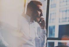 Γενειοφόρο άτομο που κάνει την κινητή κλήση στη θέση εργασίας Τύπος που φαίνεται έξω το πανοραμικό παράθυρο και που χρησιμοποιεί  Στοκ φωτογραφίες με δικαίωμα ελεύθερης χρήσης