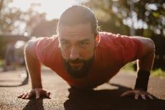 Γενειοφόρο άτομο που κάνει την ώθηση UPS στην υπαίθρια γυμναστική στοκ φωτογραφίες