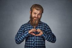 Γενειοφόρο άτομο που κάνει τη χειρονομία καρδιών με τα δάχτυλα στοκ εικόνα
