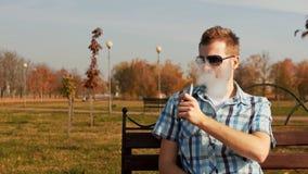Γενειοφόρο άτομο που καπνίζει ένα ε-τσιγάρο και τα χτυπήματα ένα σύννεφο του ατμού απόθεμα βίντεο