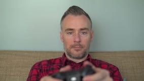 Γενειοφόρο άτομο που παίζει εν λευκώ ένα τηλεοπτικό παιχνίδι απόθεμα βίντεο