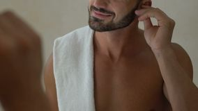 Γενειοφόρο άτομο που χρησιμοποιεί την πατσαβούρα βαμβακιού για να καθαρίσει τα αυτιά του στο λουτρό, υγιεινή αυτιών, υγεία φιλμ μικρού μήκους
